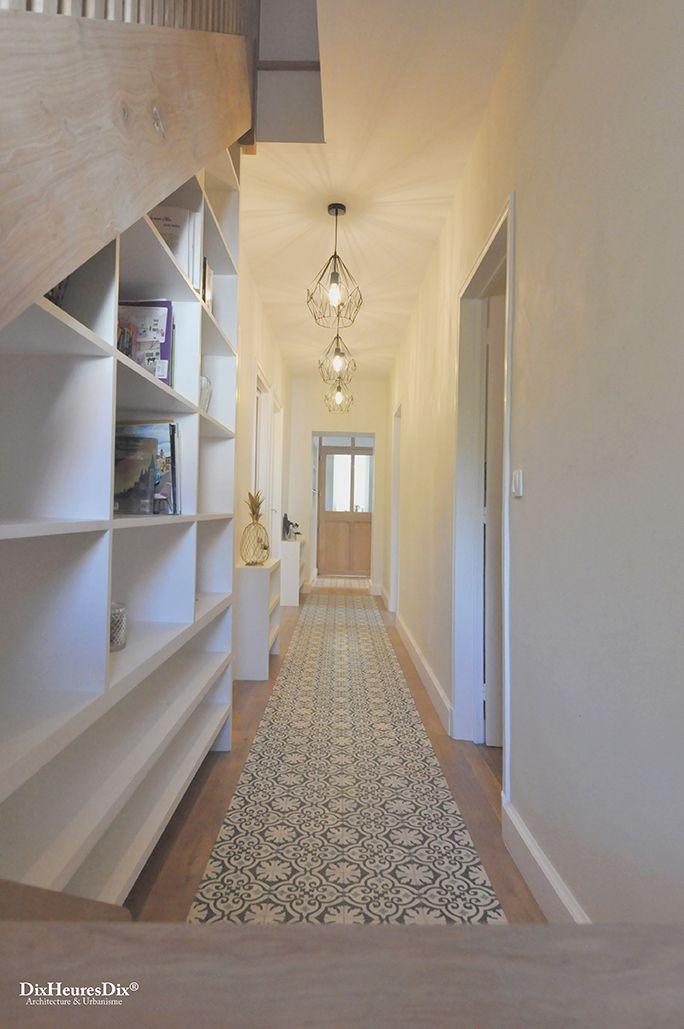 Couloir vu de l'escalier avec bibliothèque incrustée et un carrelage