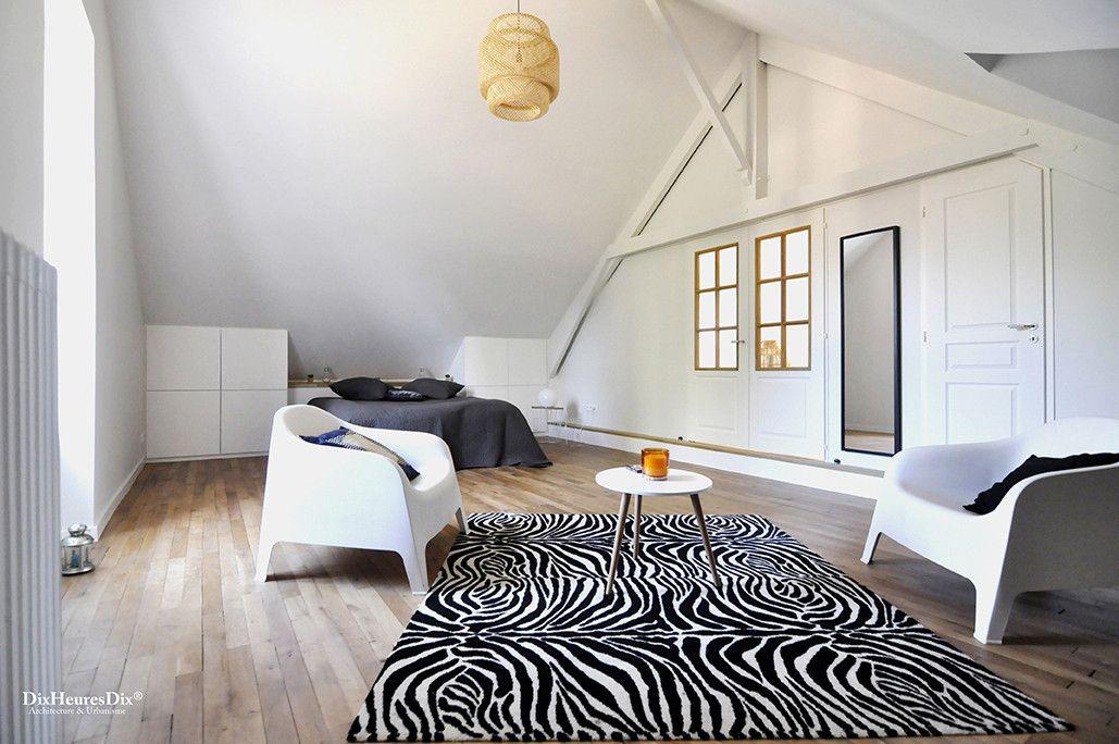 Chambre parentale avec coin détente aménagé comme un mini salon dans une résidence secondaire