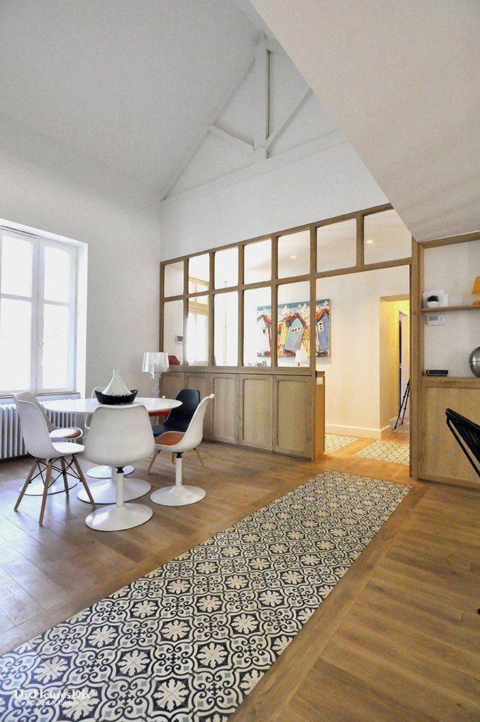 Salle à manger aménagé avec une table ronde blanche en face de la verrière dans une résidence secondaire