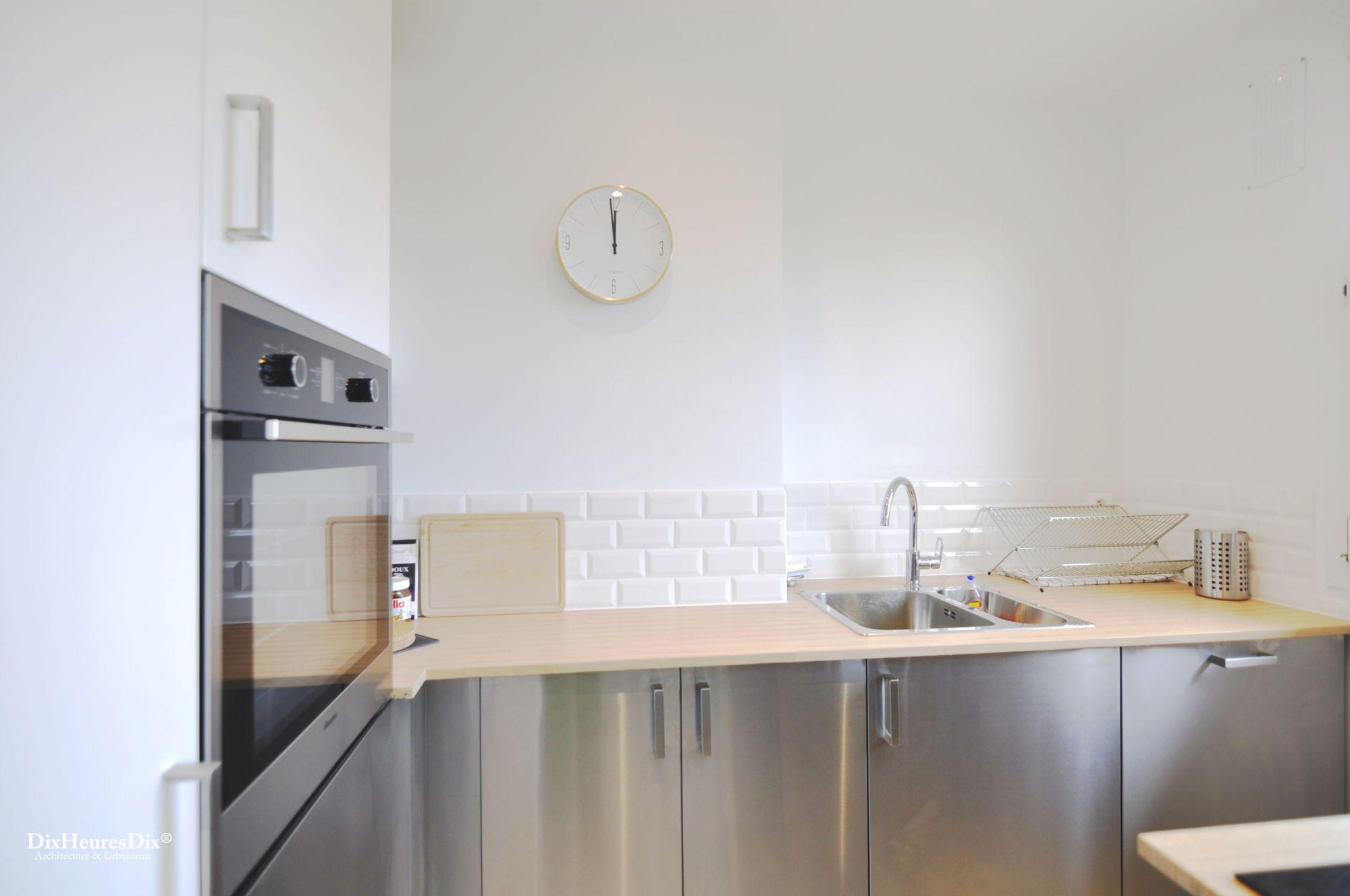 Espace cuisine en L avec un plan de travail en bois et un revêtement des placard en inox