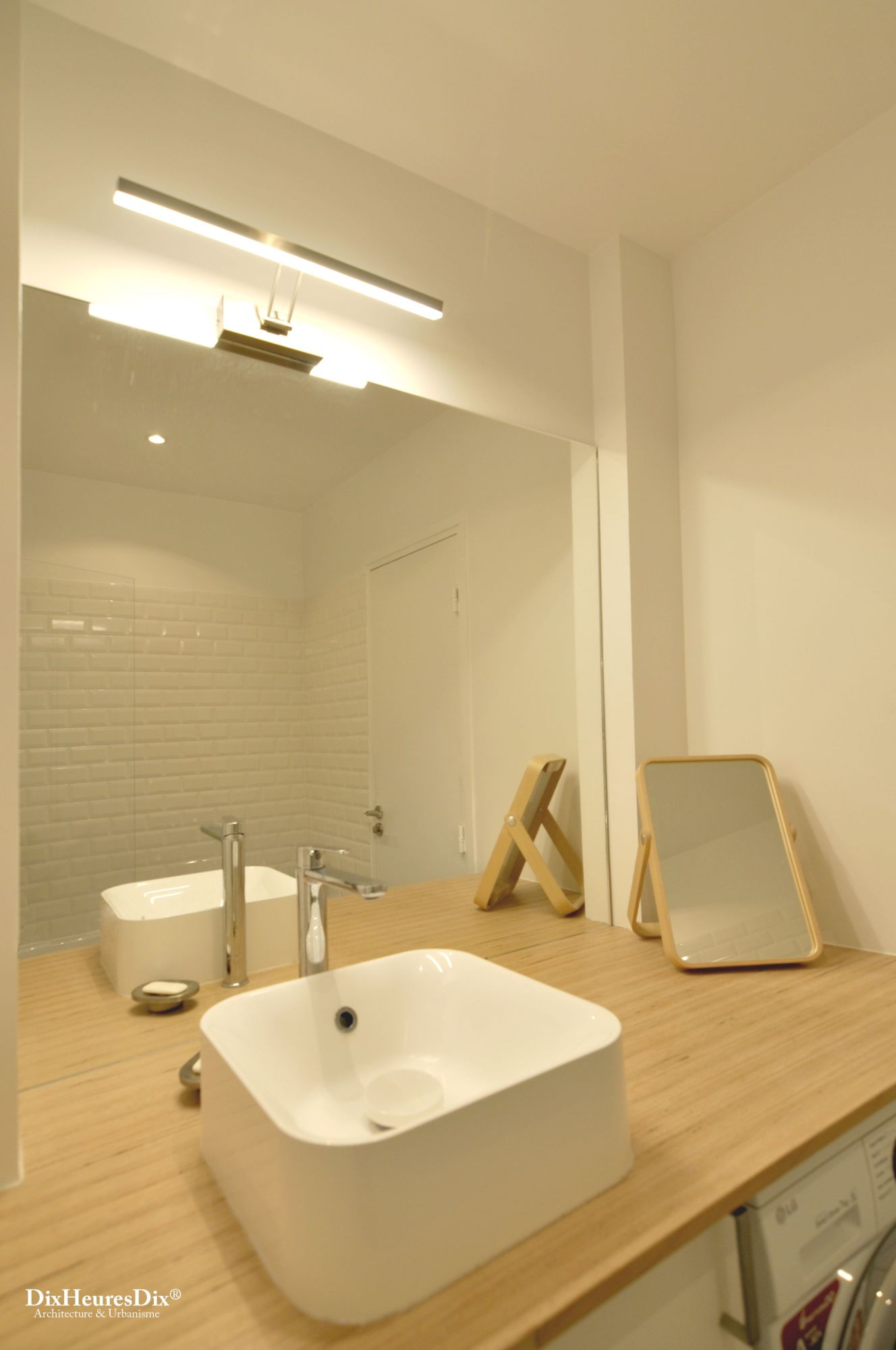 Vu sur l'espace de le plan de la salle de bain avec une grande vasque et un miroir mural