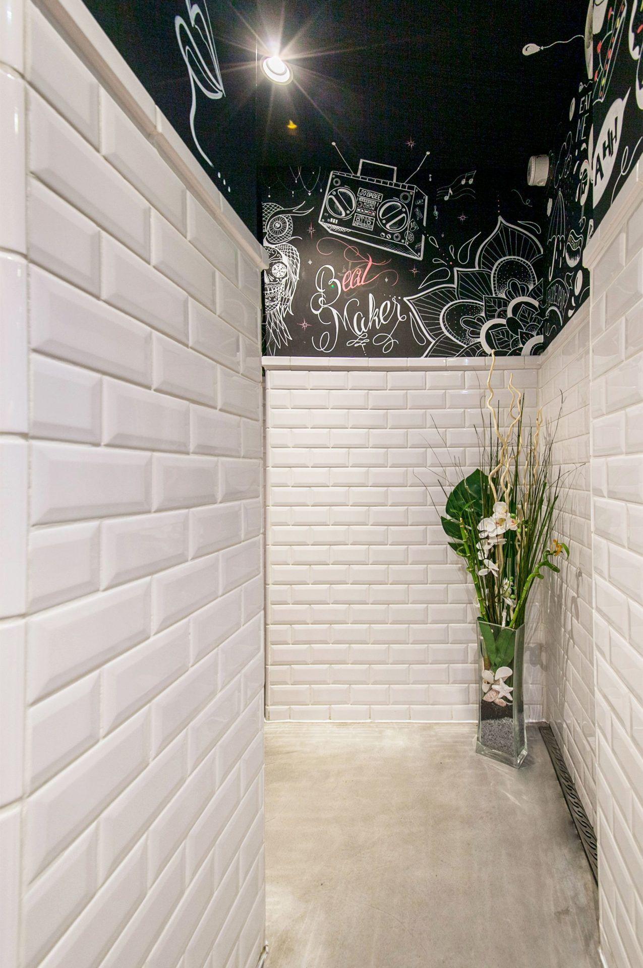 Couloir sanitaire complètement carrelé avec illustration d'un artiste