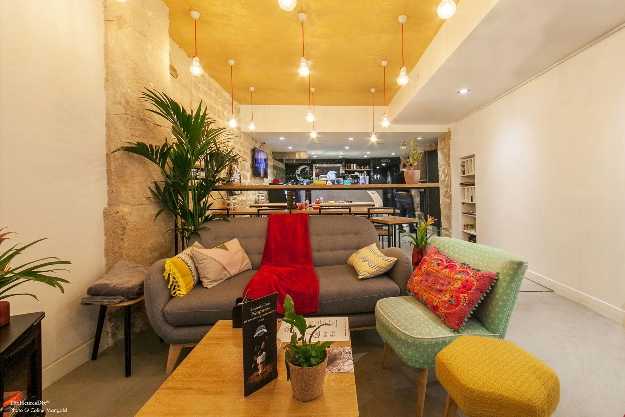 Espace canapé du restaurant aménagée avec des coussins et plaides colorés