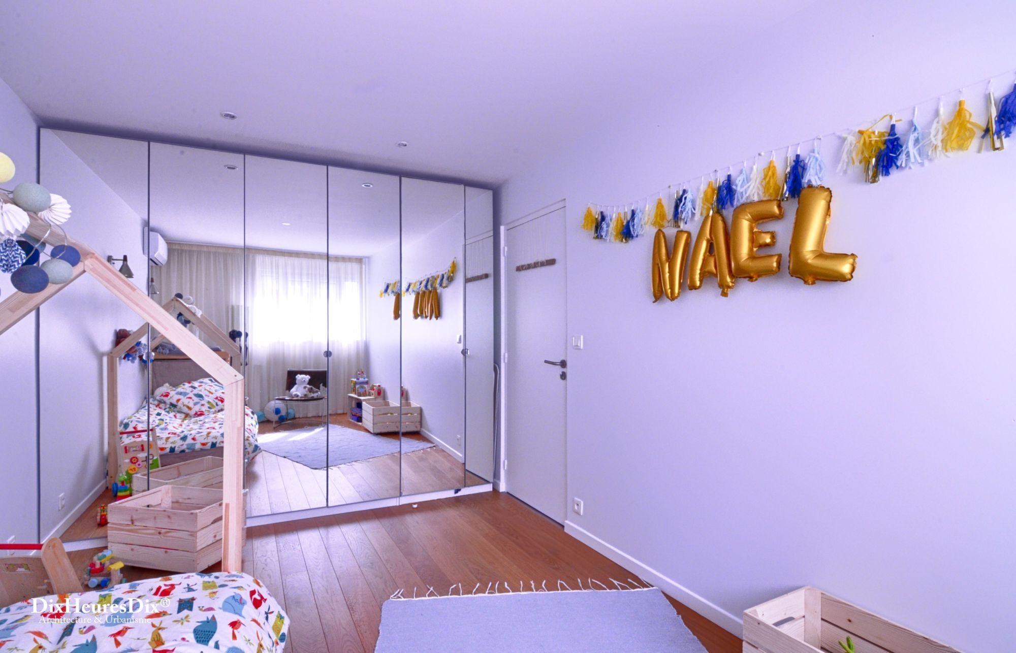 Chambre pour jeune enfant coloré se reflétant face au miroir sur un mur adjacent